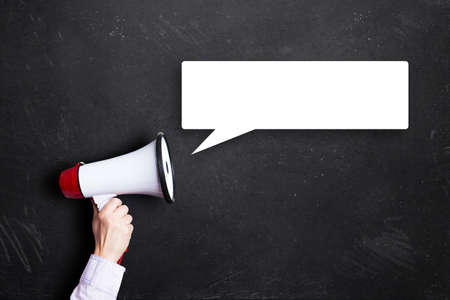 Photo for megaphone with speech bubble in front of a blackboard - Royalty Free Image