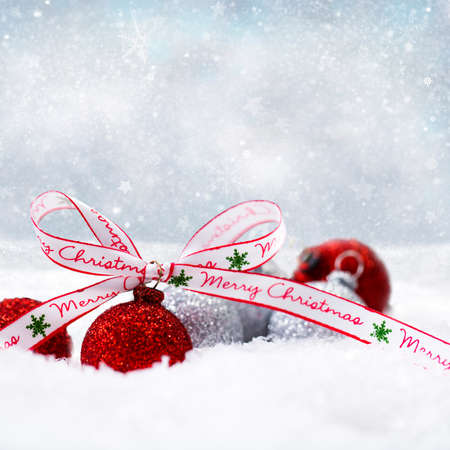 Foto de christmas balls in the snow with a merry christmas bow - Imagen libre de derechos
