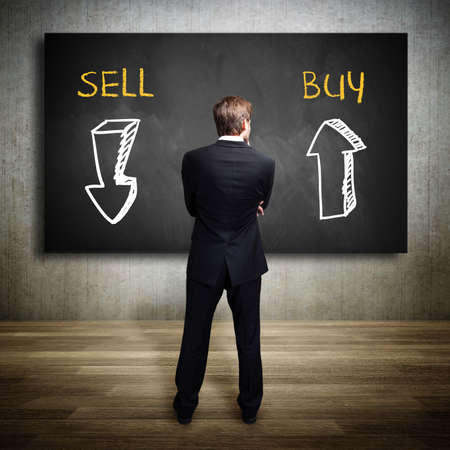 Foto de businessman standing in front of a blackboard trying to decide whether to buy or to sell - Imagen libre de derechos