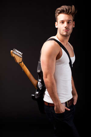 Photo pour attractive man with a guitar on black background - image libre de droit