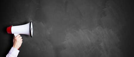 Photo pour hand with a megaphone in front of an empty blackboard - image libre de droit