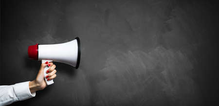 Photo for hand with a megaphone in front of an empty blackboard - Royalty Free Image