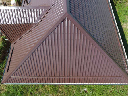 Foto de The roof of corrugated sheet. Roofing of metal profile wavy shape. A view from above on the roof of the house. - Imagen libre de derechos