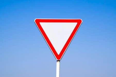Foto de Road signs, give way. Sign on a blue background. - Imagen libre de derechos
