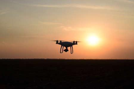 Foto de Quadrocopters silhouette against the background of the sunset. Flying drones in the evening sky. - Imagen libre de derechos