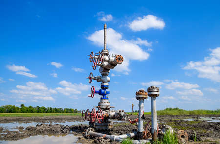 Photo pour Oil well after repair in mud and puddles. Oil well wellhead equipment. Hand valve with handwheel for opening and closing the flow line - image libre de droit
