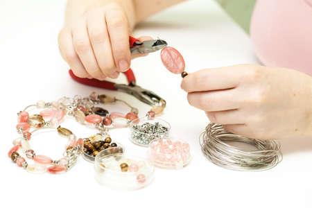 Photo pour Woman making necklase from colorful plastic beads - image libre de droit