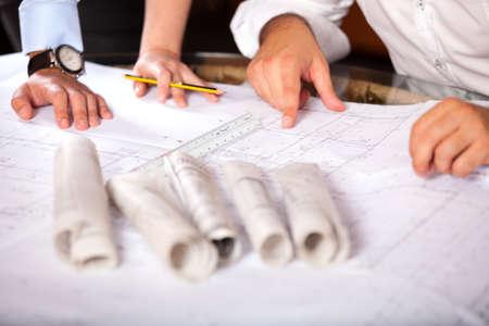 Photo pour Team of architects working on construction plans - image libre de droit