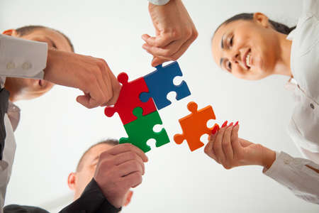 Foto de Group of business people assembling jigsaw puzzle and represent team support and help concept in office. - Imagen libre de derechos