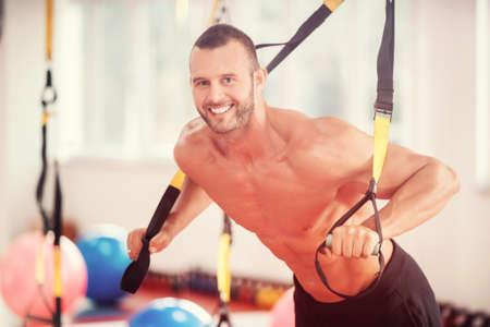 Foto de guy doing push ups training arms with trx fitness straps in the gym Concept workout healthy lifestyle sport - Imagen libre de derechos