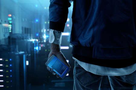 Photo pour Hacker holding mobile phone - image libre de droit