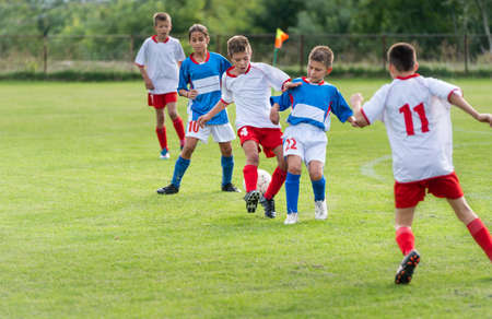 little kids playing defense in football match