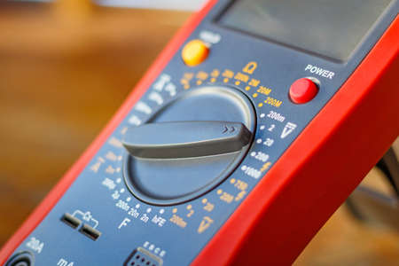 Foto de Digital multimeter on a wooden table in the workshop closeup - Imagen libre de derechos