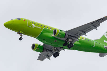 Foto de Moscow, Russia - March 17, 2019: Aircraft Embraer ERJ-170SU (ERJ-170-100 SU) VQ-BYM of S7 - Siberia Airlines going to landing at Domodedovo international airport in Moscow against gray sky - Imagen libre de derechos