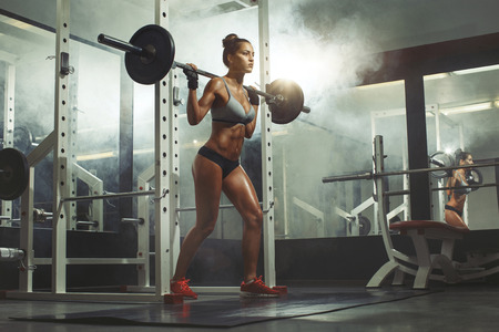 Photo for Woman lifting weight in gym - Royalty Free Image
