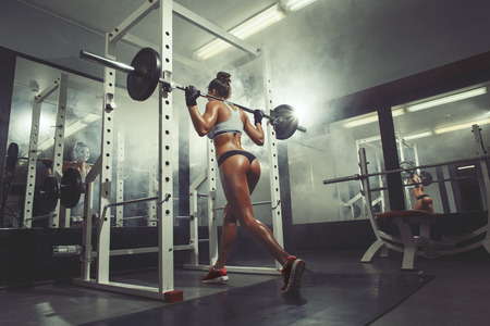 Photo pour sexy young woman resting in the gym and leaning on row of dumbbells - image libre de droit