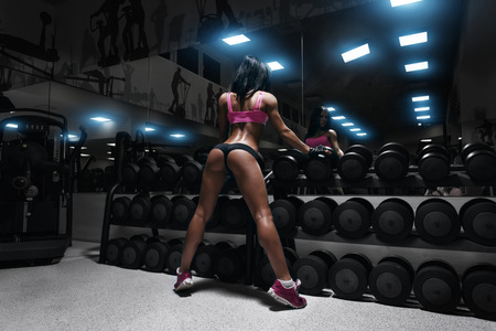 Photo for back view of sexy young brunette woman resting in the gym and leaning on row of dumbbells. Fitness girl in gym in a blue sport wear - Royalty Free Image