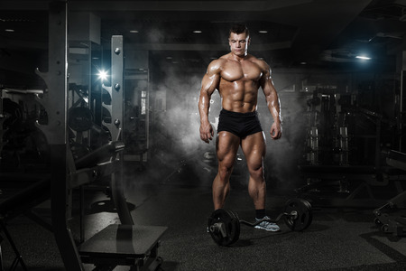 Foto de very power athletic guy standing with barbell, workout in the gym - Imagen libre de derechos
