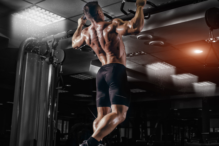 Photo pour Muscle athlete man in gym making elevations. Bodybuilder training in gym - image libre de droit