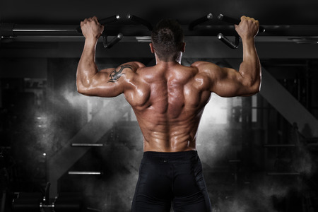 Foto per Muscle athlete man in gym making elevations. Bodybuilder training in gym - Immagine Royalty Free