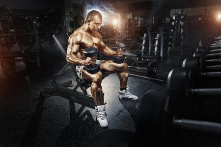 Foto de Athlete in the gym training with dumbbells - Imagen libre de derechos