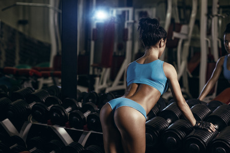 Photo pour sexy young brunette woman resting in the gym and leaning on row of dumbbells in a blue sport wear - image libre de droit