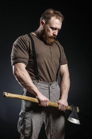 Foto de Lumberjack brutal bearded muscled man in brown shirt with suspenders on grey pants and axe on dark background - Imagen libre de derechos