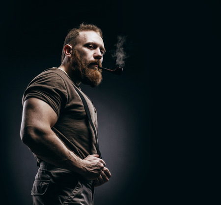 Photo for Lumberjack brutal red beard muscled man in brown shirt with smoking tube standing on dark background. Handsome man with red beard and moustache smoking pipe - Royalty Free Image