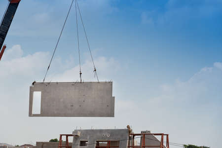 Photo for Construction site crane is lifting a precast concrete wall panel to installation building. - Royalty Free Image