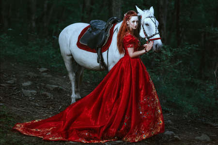 Photo for Princess in red dress dress with horse in forest - Royalty Free Image