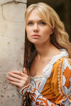 Foto de Beautiful blond woman in medieval dress walking near old building - Imagen libre de derechos