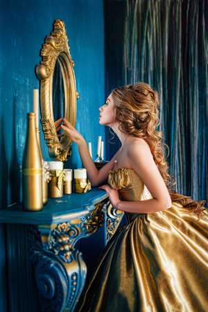 Photo pour Beautiful woman in a golden ball gown in the great blue interior - image libre de droit