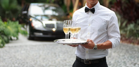 Tuxedo dressed waiter serving champagne