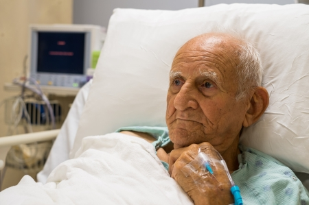 Photo pour Elderly 80 plus year old man recovering from surgery in a hospital bed  - image libre de droit