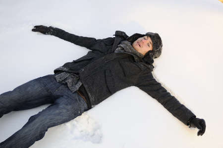 boy making snow angels