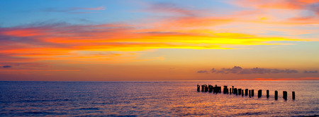 Foto de Sunset or sunrise landscape, panorama of beautiful nature, beach with colorful red, orange and purple clouds reflected in the ocean water and columns of an old pier. Taken in Naples Florida, USA. - Imagen libre de derechos