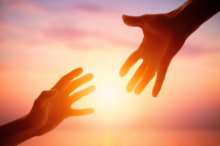 Photo pour Giving a helping hand on the background of the dawn - image libre de droit