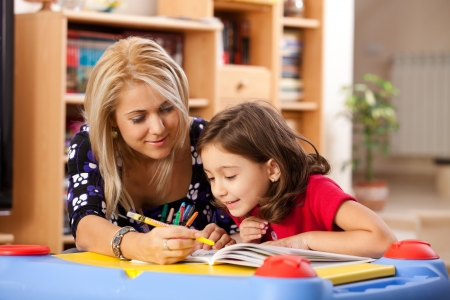 Foto de little girl and her mother drawing on a book at playtable - Imagen libre de derechos