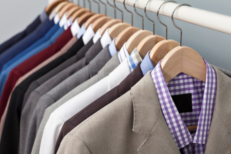 Foto de Closeup of the upper section of a row of man suits in a closet on hangers - Imagen libre de derechos