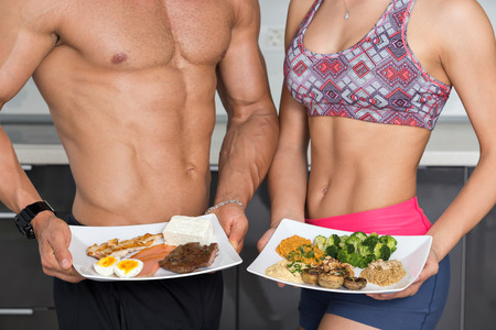 Foto de fit couple in the kitchen; animal versus plant proteins: one plate with beef, eggs, salmon, cheese and chicken grill and another with nuts, mushrooms, broccoli, lentil, hummus and quinoa - Imagen libre de derechos