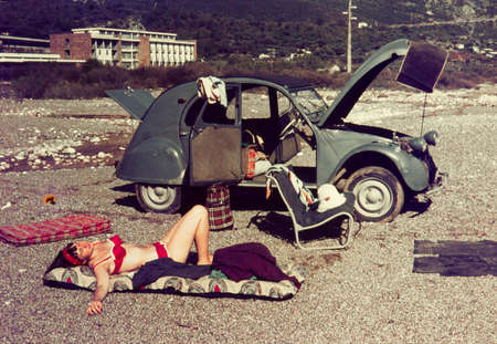 Photo pour Original vintage colour slide from 1960s, young woman relaxing on a beach with her car. - image libre de droit