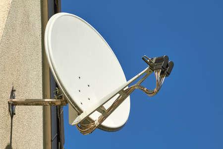 Foto de A satellite dish on a house wall. - Imagen libre de derechos