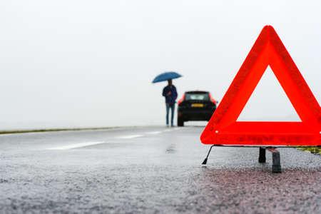 Foto de man with an umbrella besides his broken car alongside a road in the middle of nowhere - Imagen libre de derechos