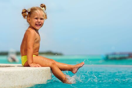 happy cute girl have a fun in pool against turquoise water of the ocean