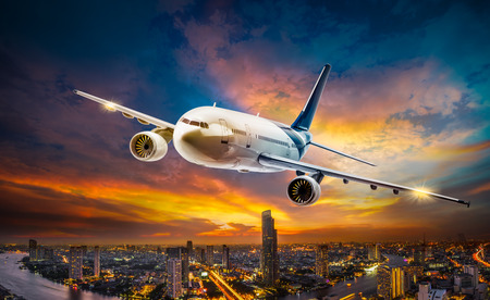 Foto de Airplane for transportation flying over the night scene city on beautiful sunset background - Imagen libre de derechos