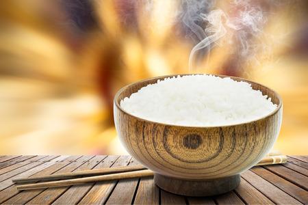 Foto de Cooked rice in wooden bowl and chopsticks with smoke on table - Imagen libre de derechos