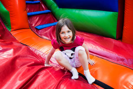 Foto de Happy little girl having lots of fun on a jumping castle while sliding. - Imagen libre de derechos