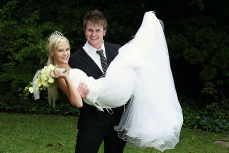Photo for Handsome bridegroom carrying his beautiful bride in his arms - Royalty Free Image