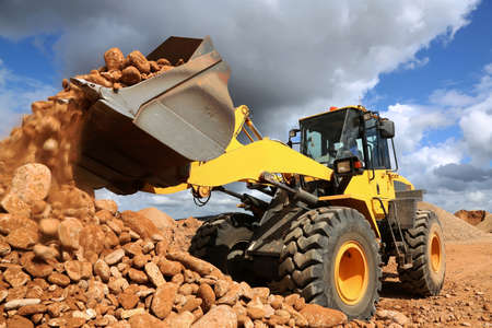 Photo pour Front end loader dumping stone and sand in a mining quarry - image libre de droit