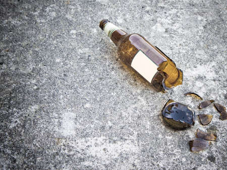 Photo pour Shattered brown beer bottle resting on the ground: alcoholism concept - toned image - image libre de droit